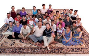 Richard and weavers in Azerbaijan sitting on a custom-made 20 x 22 ft Serapi carpet