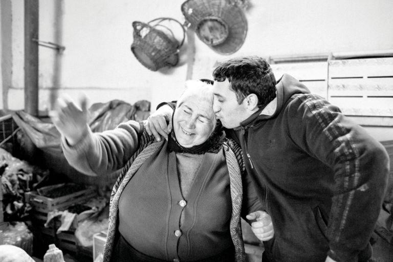 A son gives his mother an impromptu kiss. Teze Bazaar, 2014
