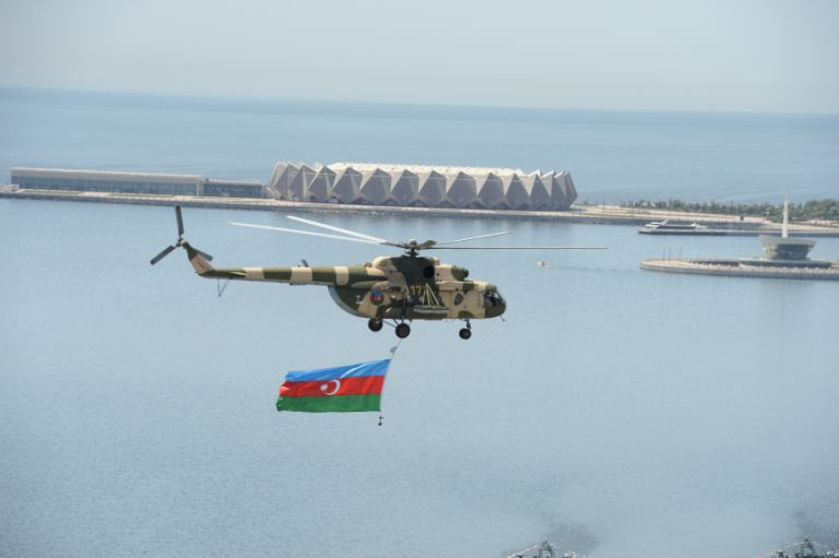 A military helicopter flies the flag above Baku Bay. Photo: Azertaj