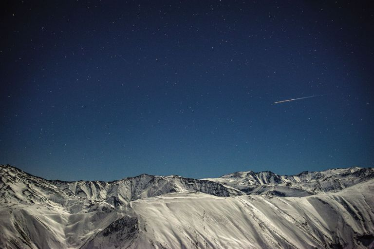 A shooting star flies over the Greater Caucasus Mountains, seen from Qaleykhudat village